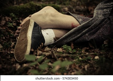 Feet of murder victim wrapped in sheets on leafy ground with one sneaker and one barefoot