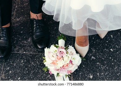 feet of the newlyweds. feet newlyweds marble floor. honeymoon shoes. the bride's bouquet