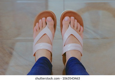 Woman's feet. Nude colours. Horizontal photo, brown background. Long fingers