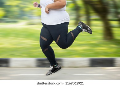 Feet of obese woman doing exercise while sprinting on the asphalt road with fast motion