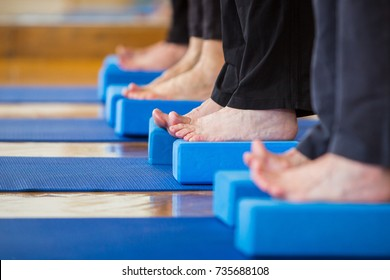 Feet of older people raising their toes on yoga mats and blocks in blue color.