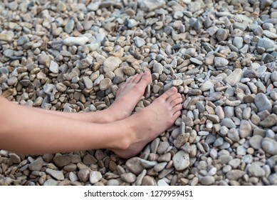 feet on beach with many stones