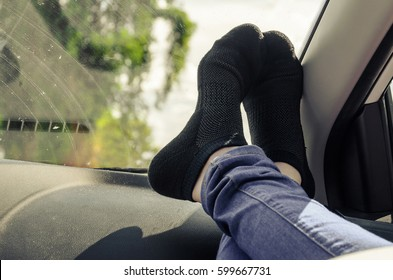 Feet on the dashboard of the car with black socks.