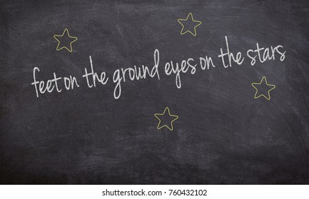 feet on the ground eyes on the stars chalk handwritten text on a black board with stars illustration