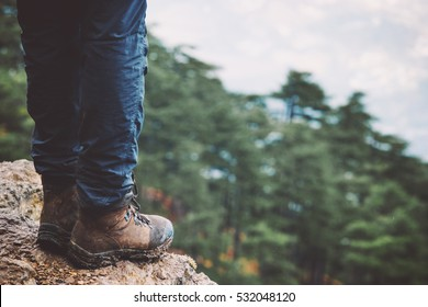 Feet on rocky cliff edge with forest aerial view Travel Fashion Lifestyle adventure vacations concept trekking boots