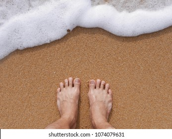 Feet on sand and wave in summer time. Man barefoot in ocean water on vacation travel. Feel happy and relax.