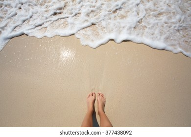 Feet on sea beach, wave with sea foam. Summer, heat, sunny day travel, freedom, enjoy and relaxation