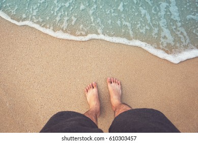 Feet on sea sand and wave, Vacation on ocean beach, Summer holiday.