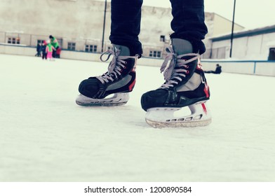 feet on the skates of a person rolling on the ice rink on the background of the ice rink in the open air. old sports hockey skates. on a man's leg. place for text,