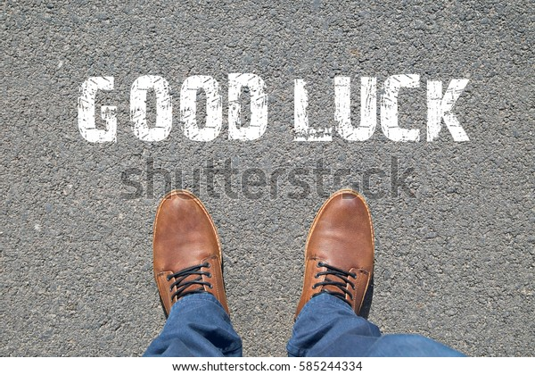 Feet on the street with text GOOD LUCK