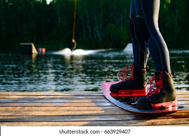 menâ??s feet on a wakeboard On the lake
