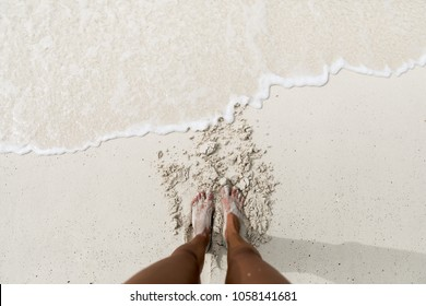 Feet on a white sand beach