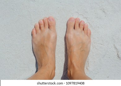 Feet on the white sand of the island.