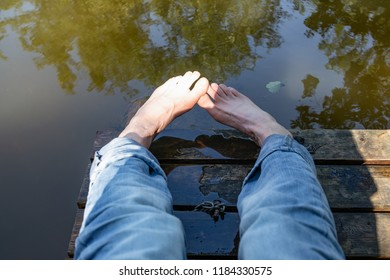 Feet over the Krutynia river. Holidays on a  pier, jetty , playing with water. Water massage. Pleasure, nice feeling. Polish Masuria Lake Region.