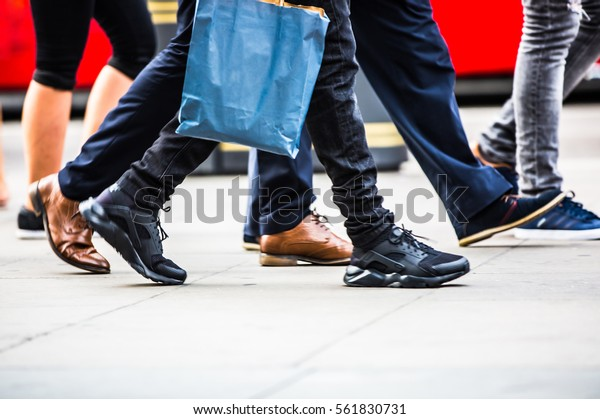 Feet of pedestrians walking on the crosswalk in Oxford street, London. Modern life, travel and shopping concept