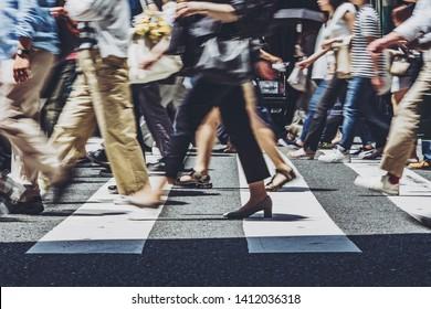 Feet of people crossing a pedestrian crossing