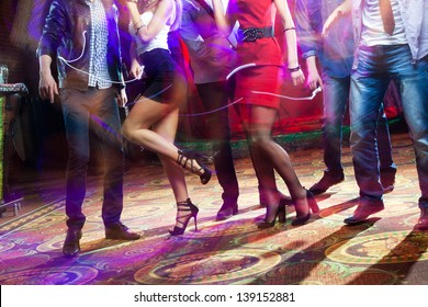 feet of people dancing on a club party. unrecognizable