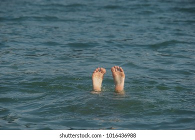 Feet of a person looking out of the water up side down.