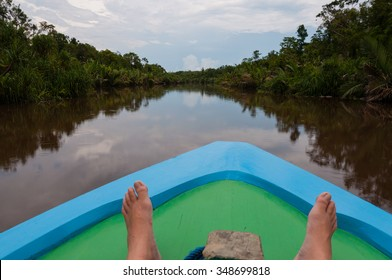 Feet of a person on boat on a river with reflection in the jungle of Kalimantan in Borneo Indonesia