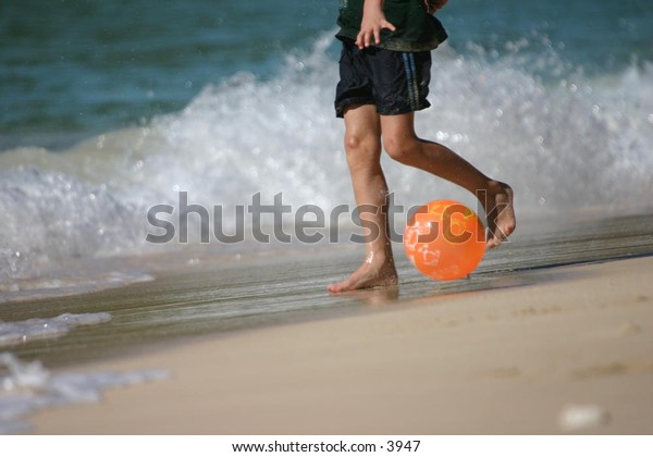 feet playing ball on a sandy beach