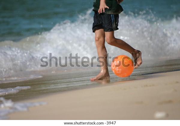 feet playing ball on a sandy beach