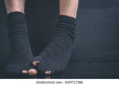 The feet of the poor debtor's in black holey socks on a black background