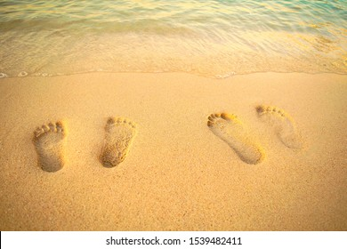 Feet prints on the sand of the beach with sea wave. Top view. Two people foot marks on sand.