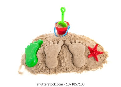 Feet prints and plastic toys at the beach isolated over white background