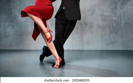 Feet of professional tango dancers in dancing movement on bright background indoors