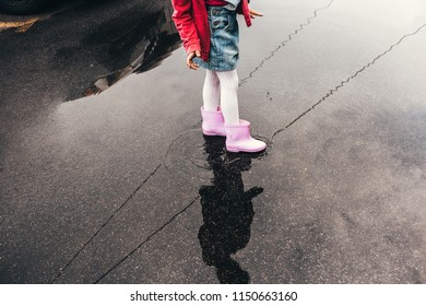 feet in puddles in rubber boots