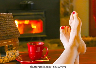 Feet Resting by the Fireplace With a Steaming Hot Cup of Tea