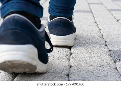 Feet in running shoes are walking forward on stony road. Concept of leaving, loneliness or passing away