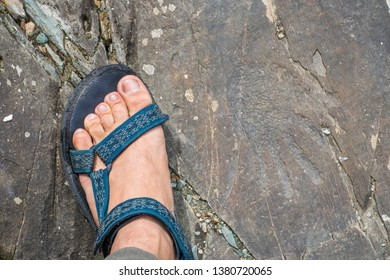 Feet in sandal and rock petroglyphs in the tract Kalbak-Tash. Petroglyphs of different historical periods: from the Neolithic to the ancient Turkic era. Altai Mountains. Russian summer in Siberia.