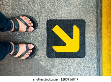 Feet in the sandal standing at the arrow sign. BTS station that have a yellow arrow sign to show passenger where they should stand while waiting for BTS. Bangkok Transportation concept. - Image.