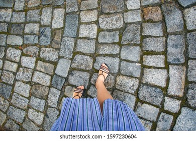 Feet in sandals on a cobblestone pavement background