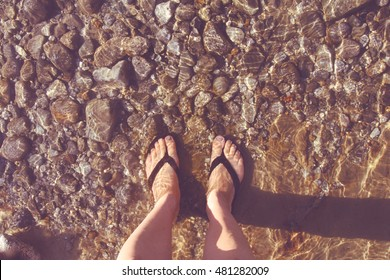 Feet in a shallow, clear lake bed.