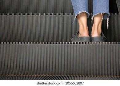 Feet in shoes standing on the escalator in the shopping mall,  view in vintage style and copy space.