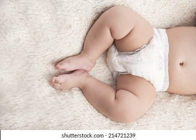 feet of a six months old baby wearing diapers lying on the bed at home