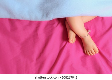 feet sleeping baby sticking out from under the blanket, Photo of asian baby boy feet under blue blanket on pink sheet with copy space, Toddler wearing silver baby anklets