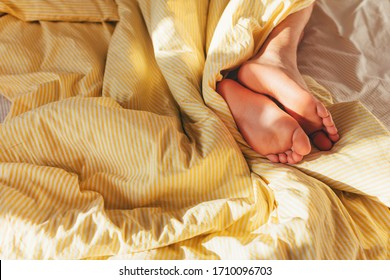 The feet of a sleeping man in the striped yellow bed linen. Sunny bedroom. Good morning
