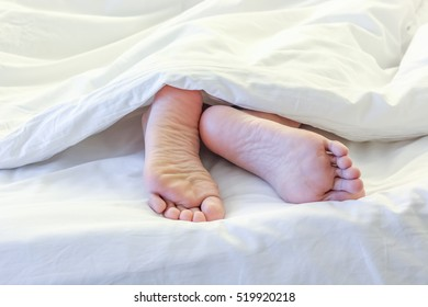 Feet of sleeping woman in white bed room