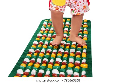Feet of small baby on a orthopedic mat carpet rug. Isolated on white background.