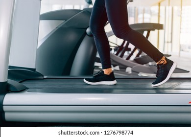Feet with sneakers of female runner / jogger running on treadmill indoors in action - with motion blur