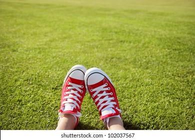 Feet in sneakers in green grass