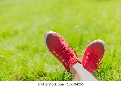 Feet in sneakers in green grass. Summer time