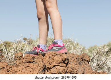 Feet in sneakers on mountains. Little girl standing on the stone at the mountains. Kid hiking in the mountains in  Canary Islands.