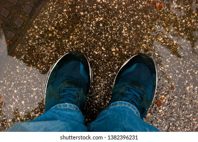 Feet with sneakers in a puddle