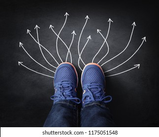 Feet with sneakers standing next to chalk arrows on blackboard taking decisions for the future