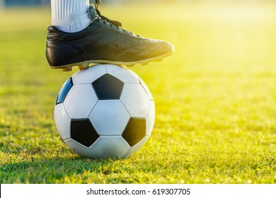 feet of soccer football player standing with the ball