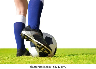 Feet of soccer player with ball on football field on white background.